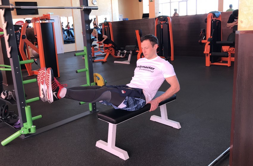 Упражнение Подтягивания ног к груди сидя на горизонтальной скамье