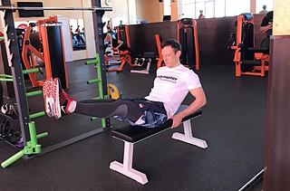Подтягивания ног к груди сидя на горизонтальной скамье