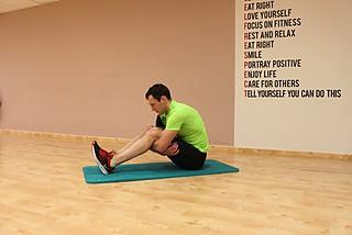 Растяжка мышц обхватывая бедра в положении сидя
