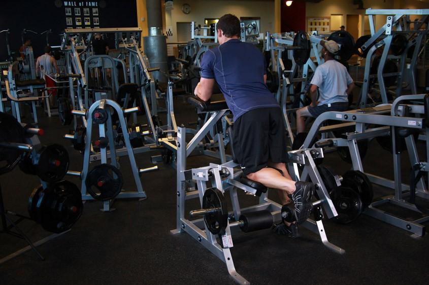 Упражнение Сгибание ног в тренажере стоя
