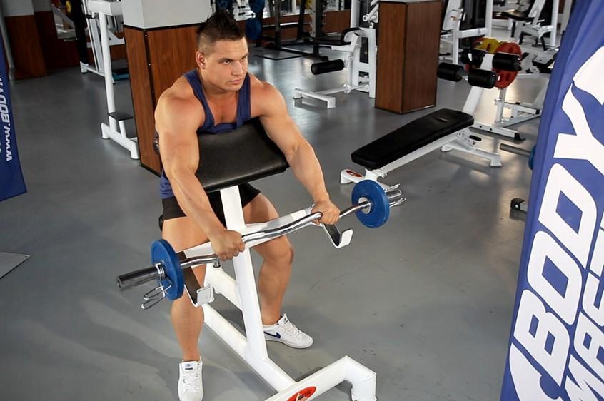Упражнение Сгибание рук на бицепс на скамье Скотта с EZ-штангой обратным хватом